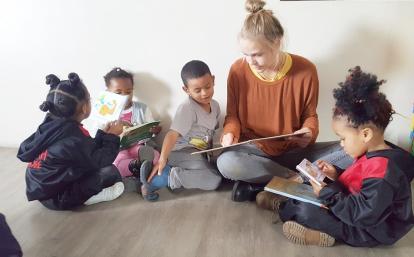 南アフリカ共和国でチャイルドケアボランティアが現地の子供たちに本の読み聞かせを行う